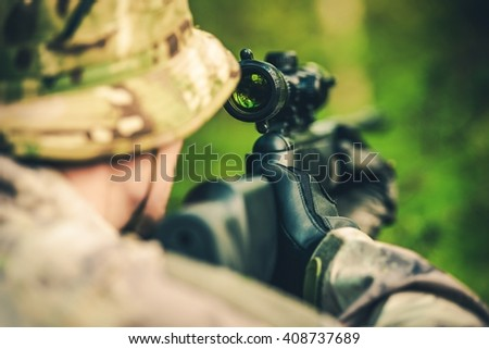 Wildlife Hunting. Camouflaged Hunter with Powerful Rifle with Scope Spotting Animals. - stock photo