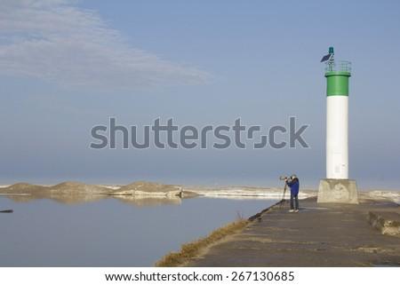 Wildlife photographer on the pier by Lake Huron lighthouse - Grand Bend, Ontario - stock photo