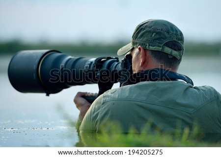 wildlife photographer outdoor in action - stock photo