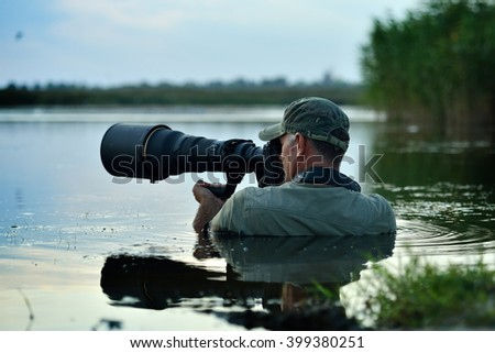 wildlife photographer outdoor, standing in the water - stock photo