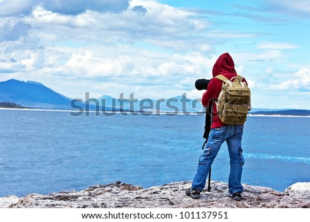 Wildlife photographer traveler enjoying ocean view from top of the mountain, backpacker hiking and taking pictures of South African landscapes, safari tour vacation, adventure and freedom concept