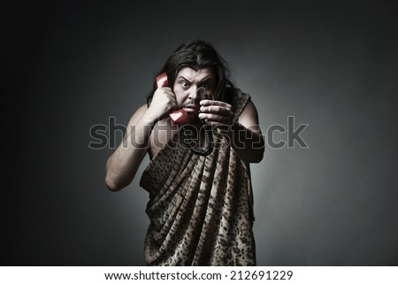 Wildman in leopard skin use retro telephone - stock photo
