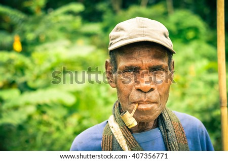 Will-will, Papua New Guinea - July 2015: Native man in blue shirt with brown cap smokes through smoking pipe and looks to photocamera in Will-will, Nuku, Papua New Guinea. Documentary editorial.