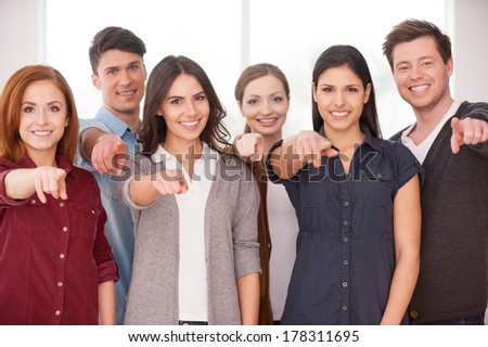 Will you join our team? Group of cheerful young people standing close to each other and pointing you - stock photo