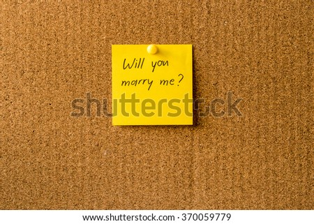 Will you marry me handwritten message on a rectangle plain note paper, attached with pin. Cork board background. A note to propose girlfriend. Valentine's day - stock photo