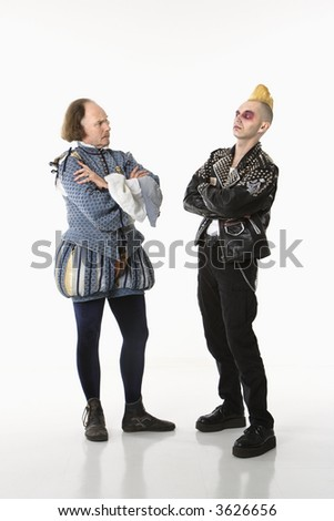William Shakespeare in period clothing and gothic punk young man standing face to face with arms crossed. - stock photo