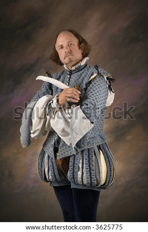 William Shakespeare in period clothing holding feather pen and looking at viewer. - stock photo