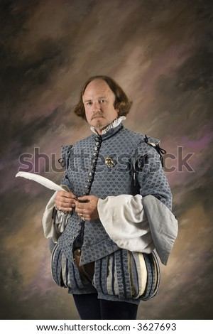 William Shakespeare in period clothing holding feather pen standing and looking at viewer. - stock photo