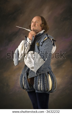 William Shakespeare in period clothing holding feather pen with thoughtful expression. - stock photo