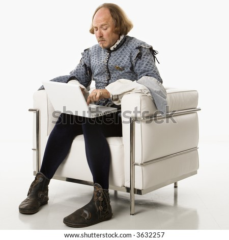 William Shakespeare in period clothing sitting on modern chair using laptop. - stock photo