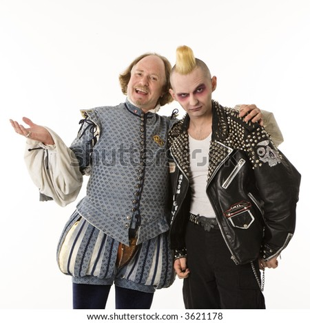 William Shakespeare smiling with arm around gothic punk young man. - stock photo
