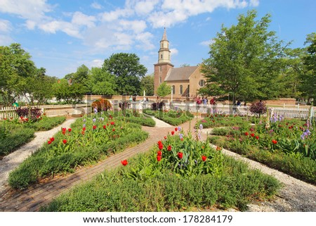 WILLIAMSBURG, VIRGINIA - APRIL 21 2012: Gardens of Colonial Williamsburg in front of Bruton Parish Church in spring. The restored town is a major attraction for tourists and meetings of world leaders.
