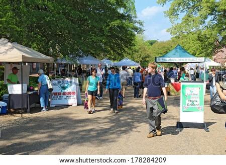 WILLIAMSBURG, VIRGINIA - APRIL 21 2012: Vendors and shoppers at the Williamsburg Farmers Market in spring. The restored town is a major attraction for tourists and meetings of world leaders. - stock photo