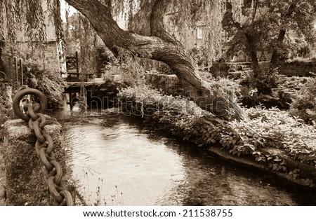 Willow tree over the idyllic canal in Pont-Aven. Brrittany, France. Retro aged photo. Sepia. - stock photo