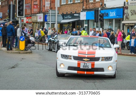 Wilmslow UK - July 9, 2013 : A Chevrolet Camaro drives sideways during the annual public gathering of local sports and super cars in affluent Wilmslow, Cheshire - stock photo