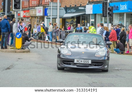 Wilmslow UK - July 9, 2013 : A Porsche drives sideways during the annual public gathering of local sports and super cars in affluent Wilmslow, Cheshire - stock photo