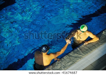 win competiotion and swimming race concept with two freiend who handshaking in pool - stock photo