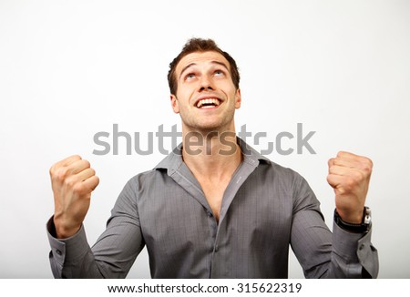 Win or succes concept - joyful man happy for his luck - stock photo