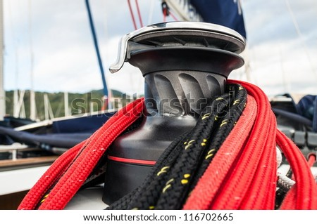Winch detail with red and black rope in a sailboat - stock photo
