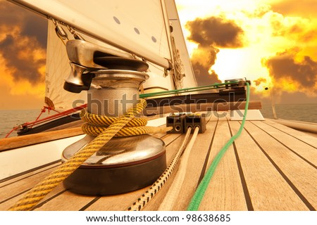 Winch with rope on sailing boat in the sea at sunset - stock photo