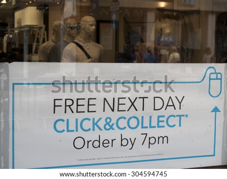 Winchester High Street, Hampshire, England - July 31, 2015: Debenhams Department Store click and collect sign in shop window - stock photo