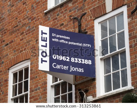 Winchester, High Street, Hampshire, England - September 4, 2015: Commercial estate agent to let sign over vacant retail units  - stock photo
