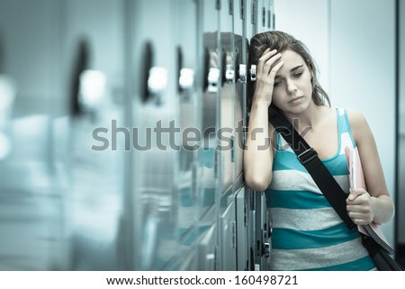 Wincing pretty student having a headache in school - stock photo