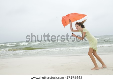 Wind and beauty girl with umbrella on the beach - stock photo