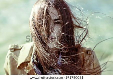 wind blowing hair of beautiful woman, outdoors, - stock photo