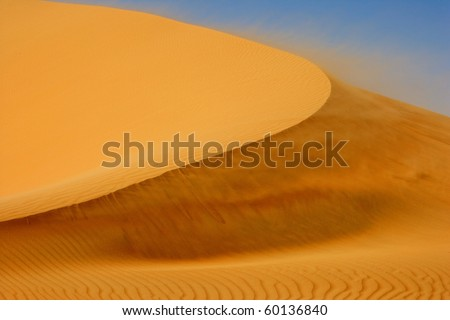 Wind blowing on a dune in the Rub al Khali or Empty Quarter. Straddling Oman, Saudi Arabia, the UAE and Yemen, this is the largest sand desert in the world. - stock photo