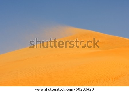 Wind blowing on the crest of a dune in the Rub al Khali or Empty Quarter. Straddling Oman, Saudi Arabia, the UAE and Yemen, this is the largest sand desert in the world. - stock photo