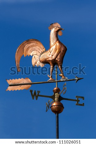 Wind cock direction on blue sky - stock photo