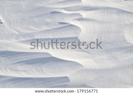 Wind created patterns on surface of  snow.  - stock photo