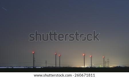 wind electric generators in the moonless starlit night - stock photo