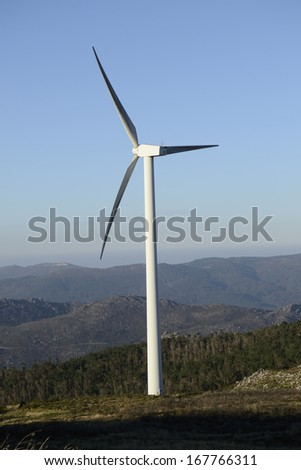 Wind energy business. Wind turbine closeup in the top of a mountain with blue sky