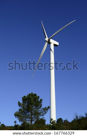 Wind energy business. Wind turbine closeup with blue sky and green trees - stock photo