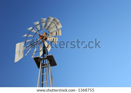 wind energy - old metal windmill against blue sky with copyspace