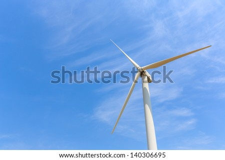 Wind energy turbine against white cloud and blue sky - stock photo
