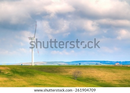 wind energy turbine are one of the cleanest, renewable electric energy source, under blue sky with white clouds. Electricity is generated by electric generators hidden inside turbine - stock photo