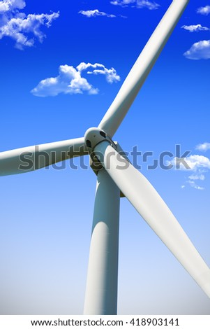 Wind energy turbine close up with blue sky