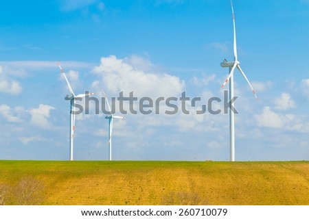 wind energy turbines are one of the cleanest, renewable electric energy source, under blue sky with white clouds. Electricity is generated by electric generators hidden inside turbine - stock photo