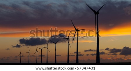 Wind energy turbines at sunset - stock photo
