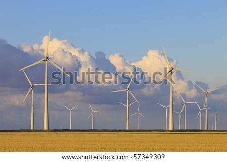 Wind energy turbines in summer with a blue sky - stock photo