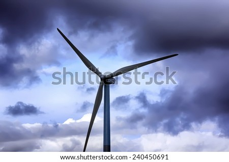 wind energy windmills in a dark storm, electric generators - stock photo