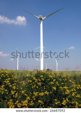 Wind Farm against blue sky with white clouds and yellow flowers - stock photo
