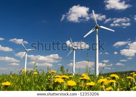 Wind Farm against blue sky with white clouds and yellow flowers on the ground - stock photo