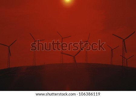 Wind farm against red sunset - stock photo