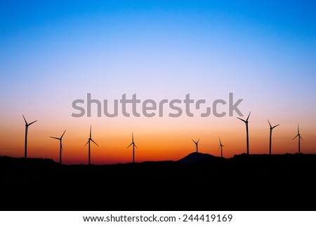 Wind farm and windmills silhouettes in sunset light. Alexigros, Larnaca district, Cyprus. - stock photo