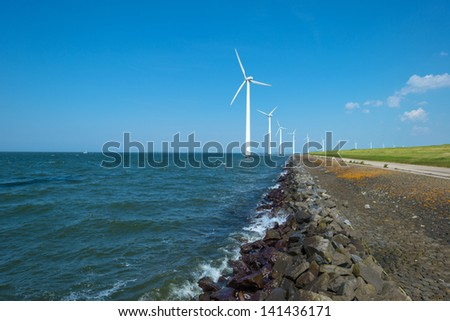 Wind farm in a lake along a sunny dam - stock photo