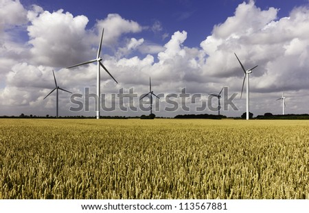 Wind farm in a wheat field and a storm brewing, near Lisset, Yorkshire, UK